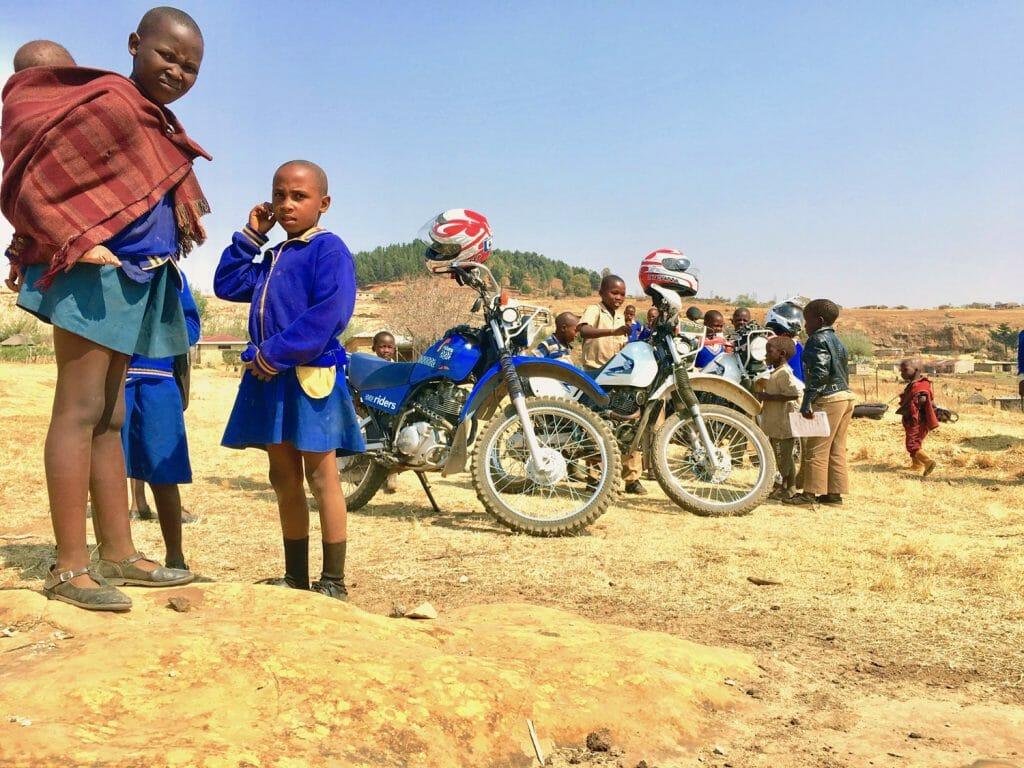 Lesotho, schoolgirls standing by motorcycles
