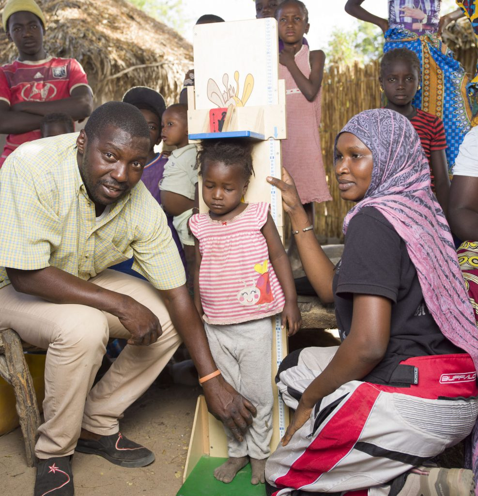 Community health worker charting children's growth.