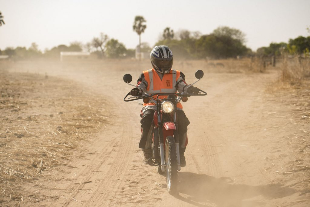 Jogob Gassama - community health worker on motorcycle, The Gambia
