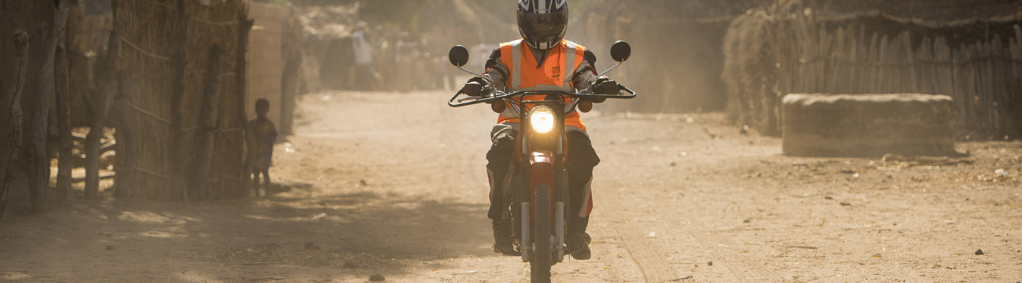 Healthworker riding motorcycle, The Gambia