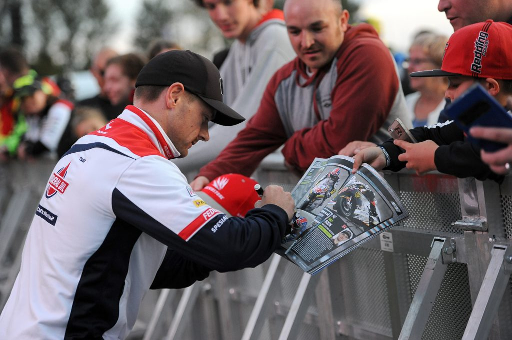 Sam Lowes signs an autograph for a young fan