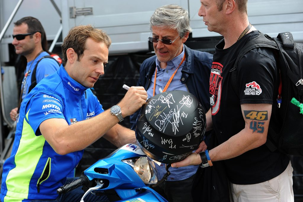 Sylvain Guintoli signs a helmet for a fan