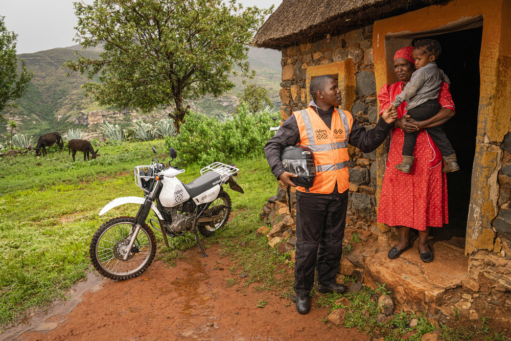 Motorcycle health worker in community with mother and baby,Lesotho, 2020